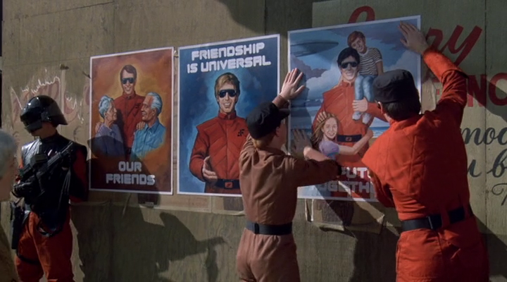Some red and brown-suited people, some of them are aliens in human disguise, posting three alien occupation propaganda posters, each bearing the message OUR FRIENDS, FIRENDSHIP IS UNIVERSAL and THE FUTURE TOGETHER respectively.